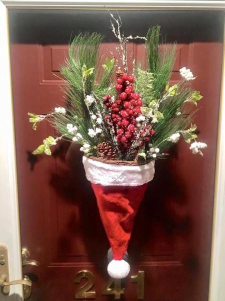 como montar una decoracion de gorros de santa para puertas con ramas navideñas